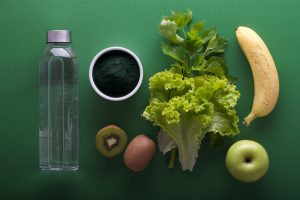 Water bottle with a side of leafy greens, a banana, a kiwi and an apple